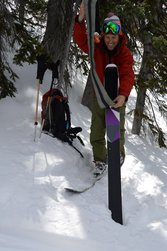 Easy there cowboy. One hand on the pole for balance while the other hand places the pre-folded skin over the tip of the ski.